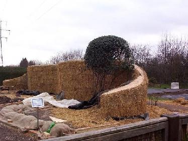 Bau einer Strohballenmauer: auf einem Fundament aus Betonsteinen werden, abgedichtet durch eine Folie, die Strohballen im Versatz gestapelt und mit Verpackungsbändern wie im lasttragenden Strohballenbau verdichtet.  © Chug's Strawbale World