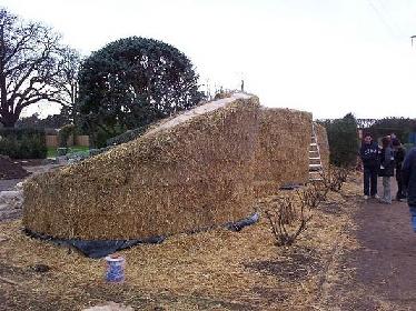 Die überstehenden Halme werden mit einem Rasentrimmer abgeschnitten und ein Hasengitter als Putzträger über die Ballengezogen und an den Schnüren befestigt.  © Chug's Strawbale World