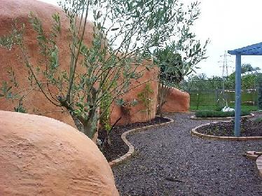Wie eine große Skulptur oder ein Steinhaus in Arizona mutet die organische Wand an, mehr als nur ein Sichtschutz.  © Chug's Strawbale World